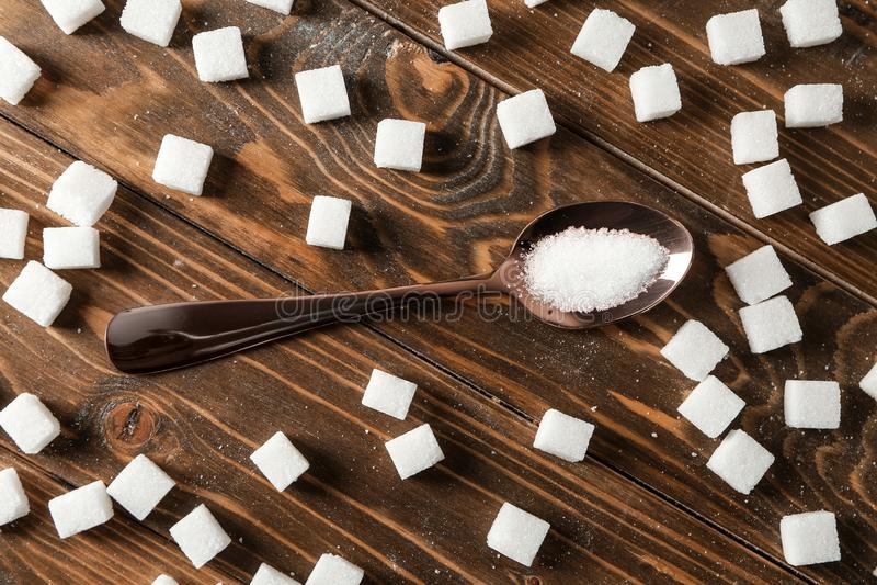Sked med socker och kuber på trätabellen royaltyfri fotografi