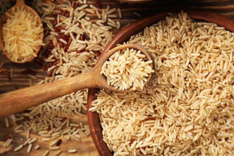 Sked och bunke med rå ris på trätabellen royaltyfri bild