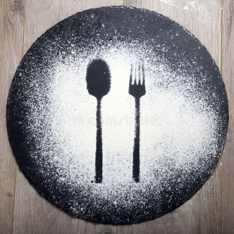 Sked- och gaffelkontur som g?ras med mj?l p? den m?rka texturbakgrunden arkivbilder