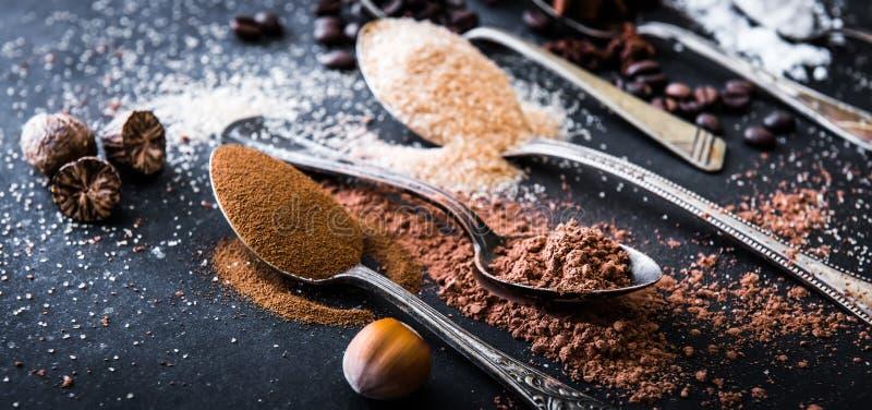 Skedar för för chokladpulverkakao och kaffe på tabellen arkivfoto