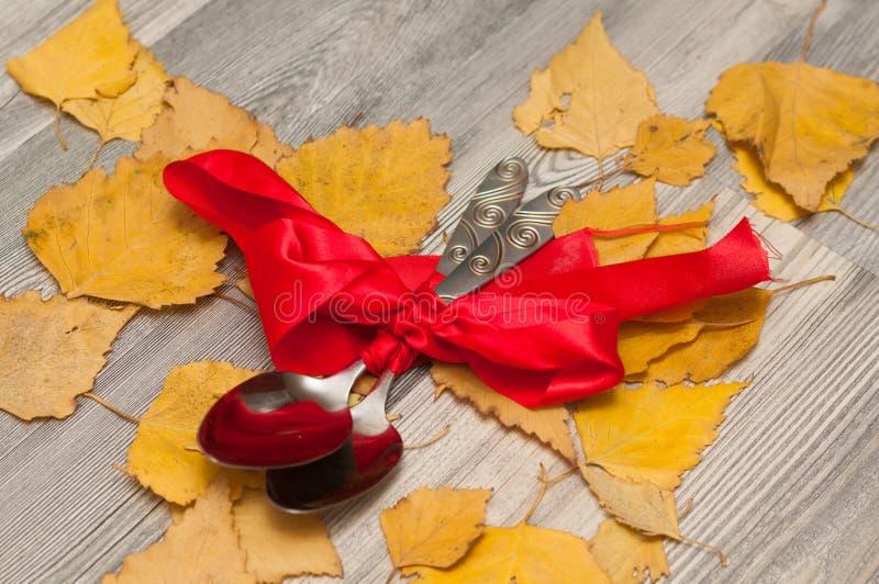 Skedar slås in i ett rött band med en pilbåge som en gåva på bakgrunden arkivfoton