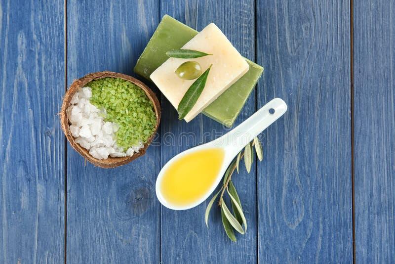 Skeden med olivolja, stänger av naturlig tvål och havet saltar på trätabellen arkivfoto