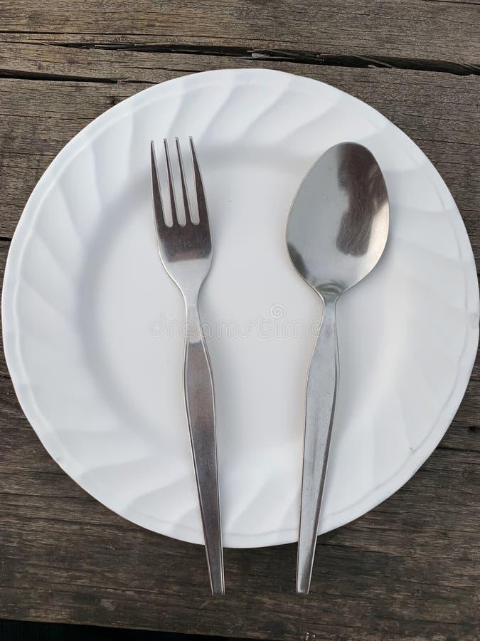 Skedgaffel och maträtt på den gamla tabellen fotografering för bildbyråer