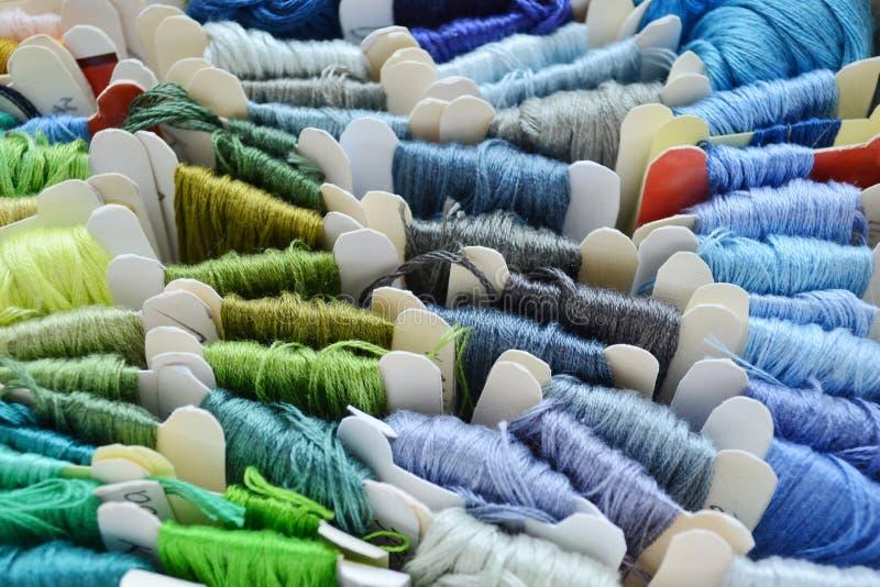 Skeins av färgrika trådar i kalla färger för broderi och att sy royaltyfria bilder