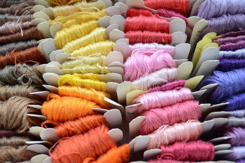 Skeins av färgrika trådar i varma färger för broderi och att sy royaltyfri foto