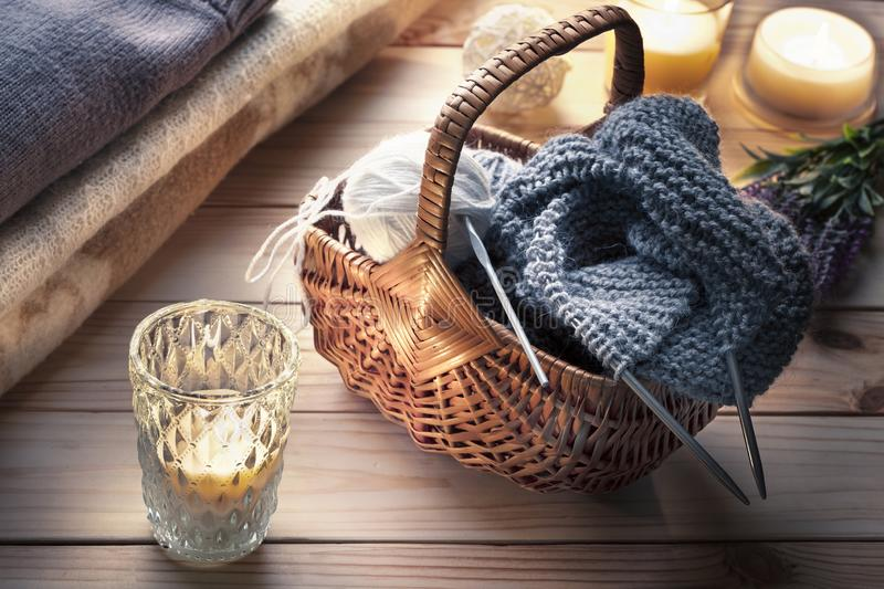 Skeins of yarn for knitting, knitting and knitting needles in wicker basket in rustic interior. Knitting or relaxation royalty free stock photos
