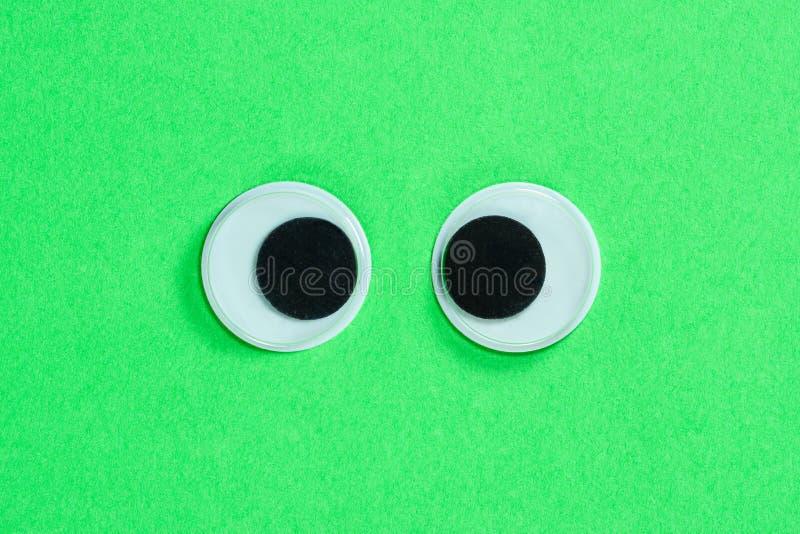 Skelögda googly ögon på grön bakgrund för neon Tokiga roliga leksaker?gon st?nger sig upp arkivbild