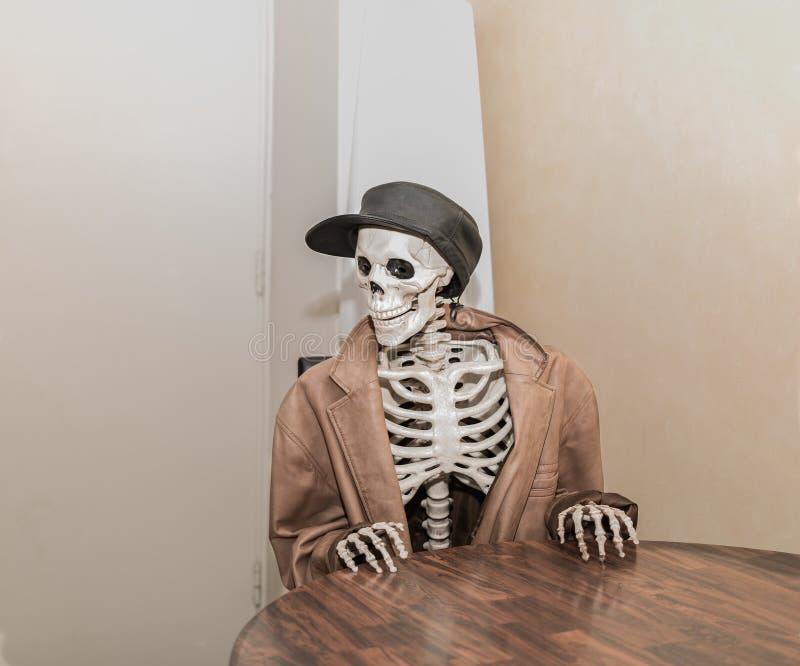 Skelet die bruin leerjasje met leerhoed dragen, die achter de lijst zitten stock afbeelding