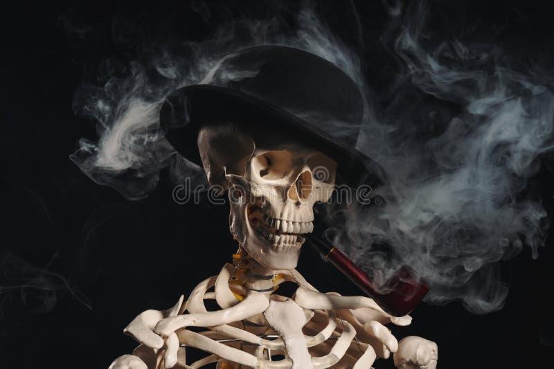 Skeleton in bowler hat smoking pipe royalty free stock photography