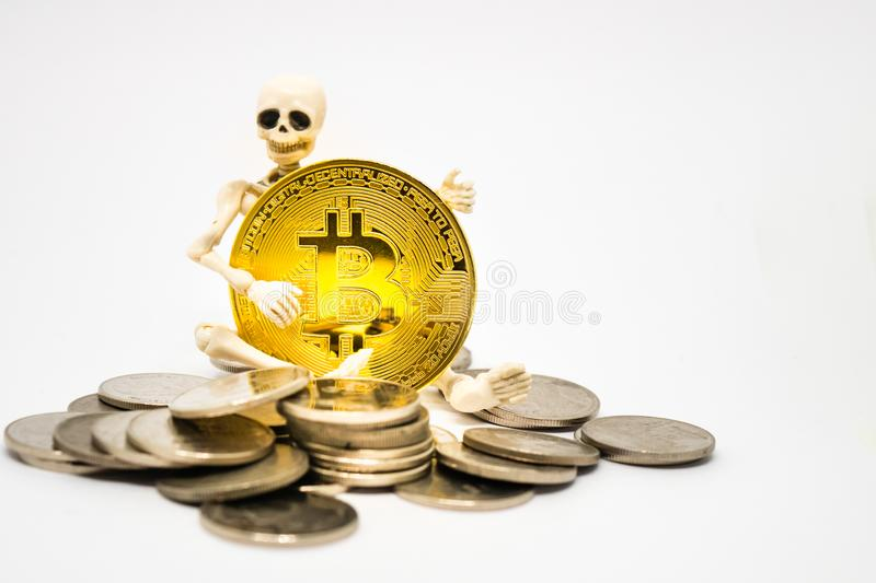 Skeleton figure holding a golden bitcoin royalty free stock photography