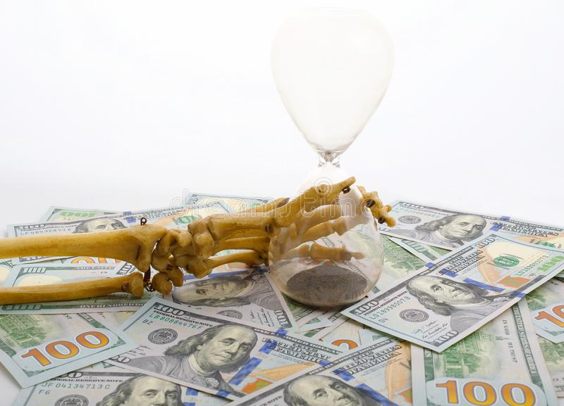 Skeleton fingers holding sand-glass placed on dollars. concept of time - money and death. royalty free stock photography