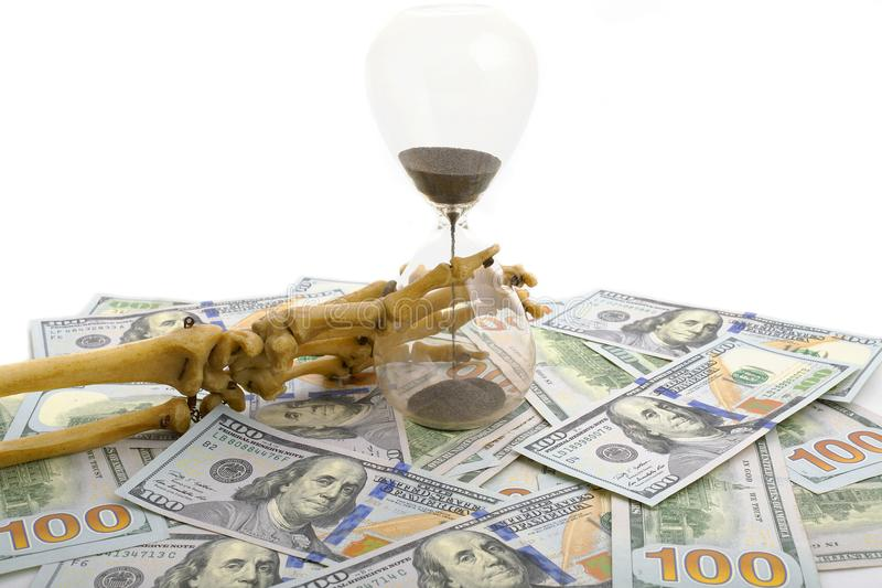Skeleton fingers holding sand-glass placed on dollars. concept of time - money and death. stock photo