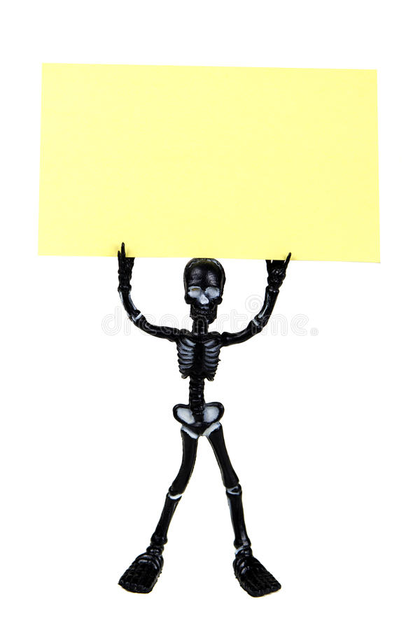 Skeleton holding a post it. Funny skeleton holding a yellow post it isolated on white royalty free stock images