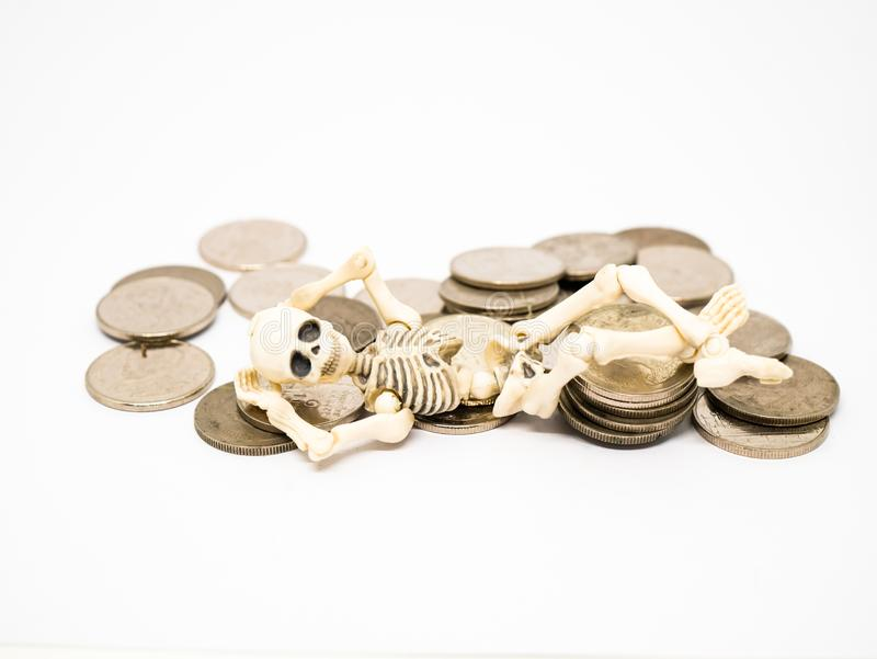 Skeleton laid on coins royalty free stock photography