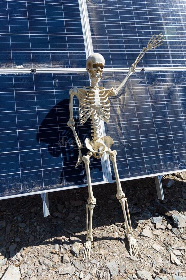 Skeleton leaning on solar panels in the desert. Nevada, bony, hands, tan, white, bone, frame, human, anatomical, halloween, science, skull, figure, power stock images