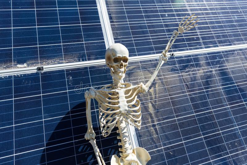 Skeleton leaning on solar panels in the desert. Nevada, bony, hands, tan, white, bone, frame, human, anatomical, halloween, science, skull, figure, power royalty free stock photo