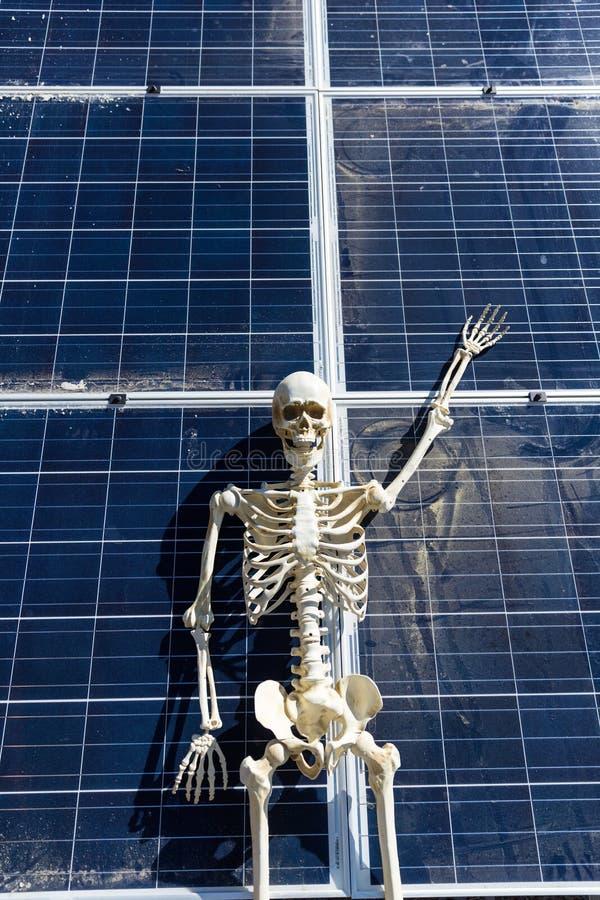 Skeleton leaning on solar panels in the desert. Nevada, bony, hands, tan, white, bone, frame, human, anatomical, halloween, science, skull, figure, power royalty free stock photos