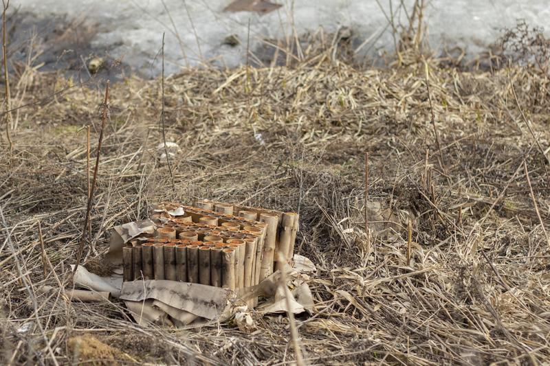 The skeleton of the New Year`s salute. Remains of burnt fireworks. Pollution, garbage in the spring on the shore of the lake pond royalty free stock image