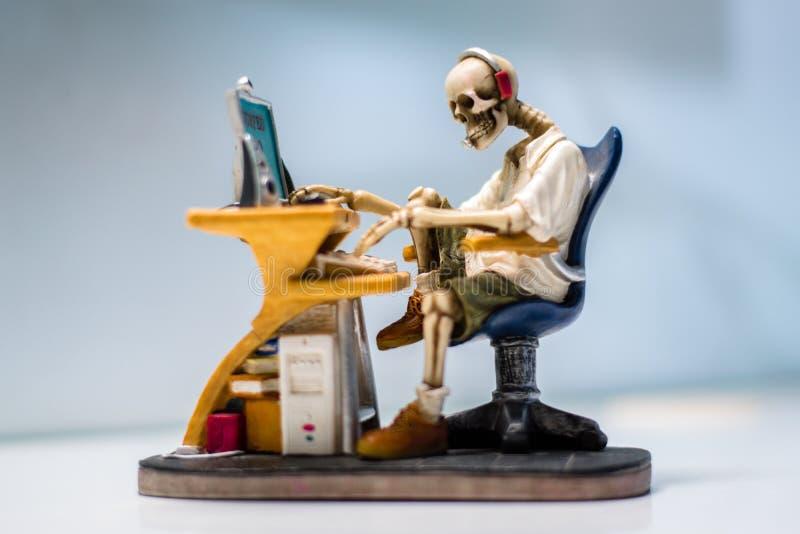 Skeleton sculpture working at computer