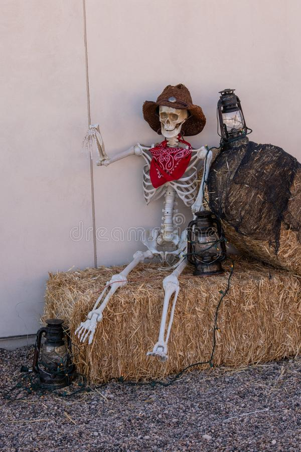Skeleton sitting on hay bales. Cute skeleton sitting hay bales with lanterns, dressed up for Halloween royalty free stock photos