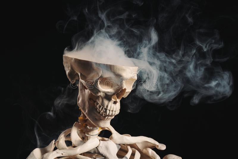 Skeleton with smoke coming out of open skull stock photo