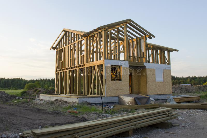 Skeleton of a wooden two-story cottage surrounded by building materials stock image