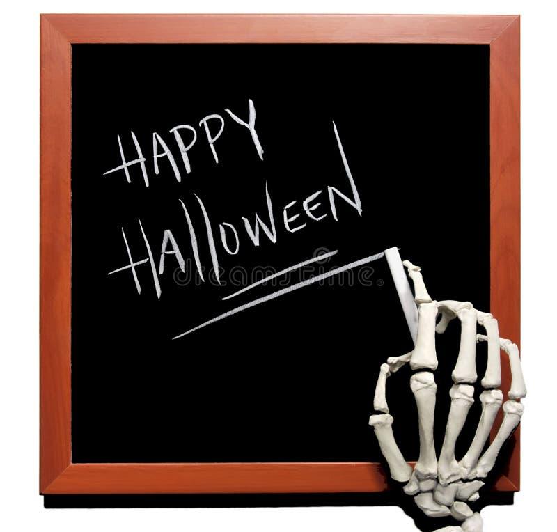 Skeleton writes Happy Halloween. On a blackboard in chalk stock photo