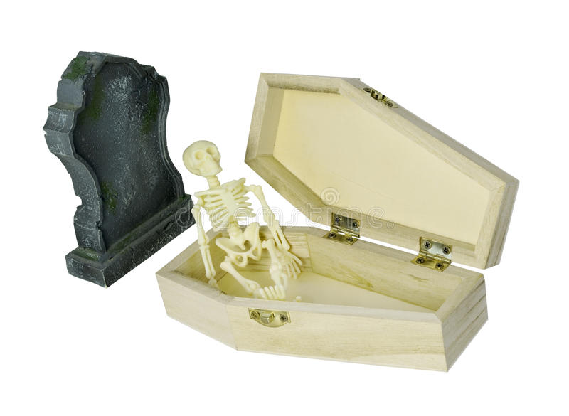 Skelett, das im Sarg nahe bei Grabstein sitzt lizenzfreie stockbilder