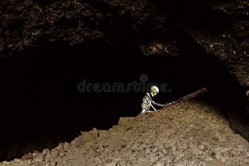 Skelett in einer dunklen Höhle im Boden, der auf Felsen kriecht lizenzfreies stockbild
