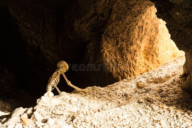 Skelett kriecht zur Sicherheit eines Bergwerkeingangs, der auf Felsen kriecht stockfotos