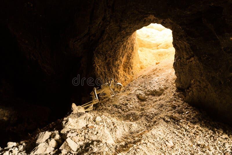 Skelett kriecht zur Sicherheit eines Bergwerkeingangs, der auf Felsen kriecht lizenzfreie stockfotografie