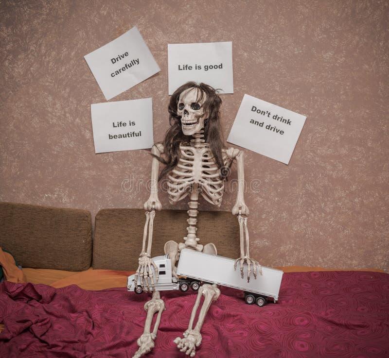 Skelettet i ett peruksammanträde på sängen med lastbilen och släpet modellerar på hans ben som lutar mot väggen med olika meddela royaltyfri bild