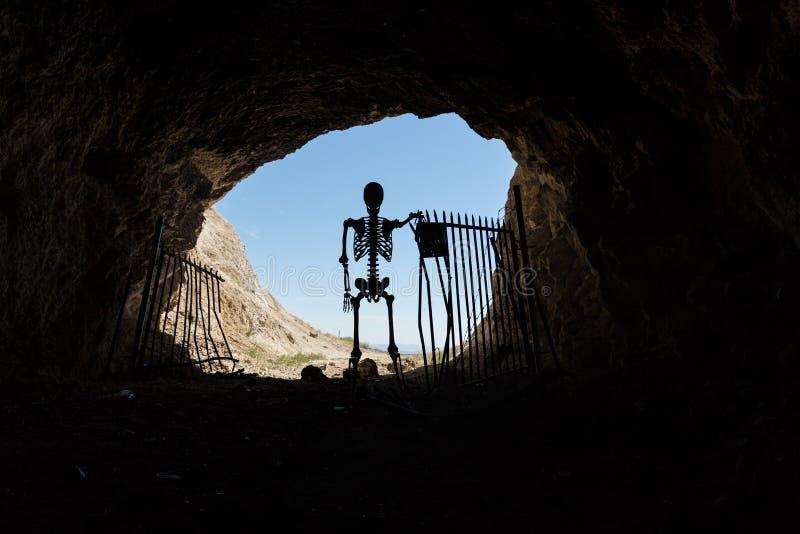 Skelettschattenbild im Mund eines mit einem Gatter versehenen Aufenthalts des Bergwerkaufenthalts heraus lebendig stockbilder