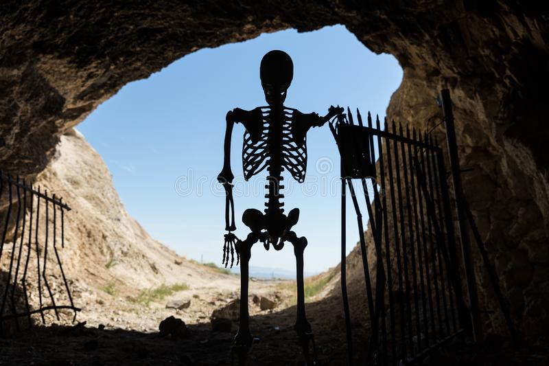 Skelettschattenbild im Mund eines mit einem Gatter versehenen Aufenthalts des Bergwerkaufenthalts heraus lebendig stockbild