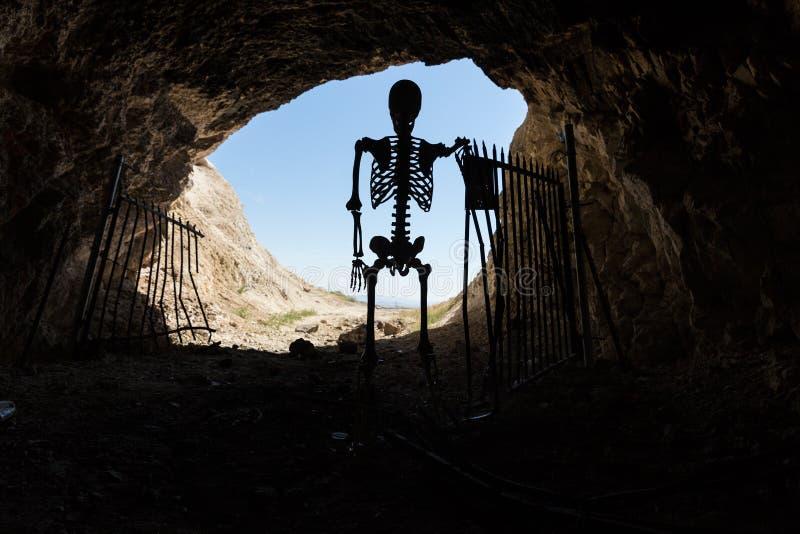 Skelettschattenbild im Mund eines mit einem Gatter versehenen Aufenthalts des Bergwerkaufenthalts heraus lebendig stockfotos