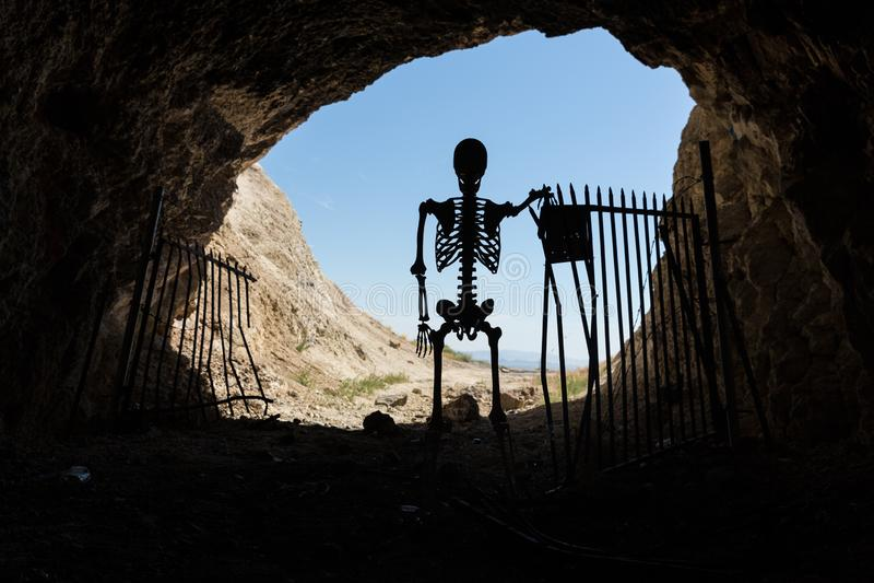 Skelettschattenbild im Mund eines mit einem Gatter versehenen Aufenthalts des Bergwerkaufenthalts heraus lebendig lizenzfreie stockfotografie