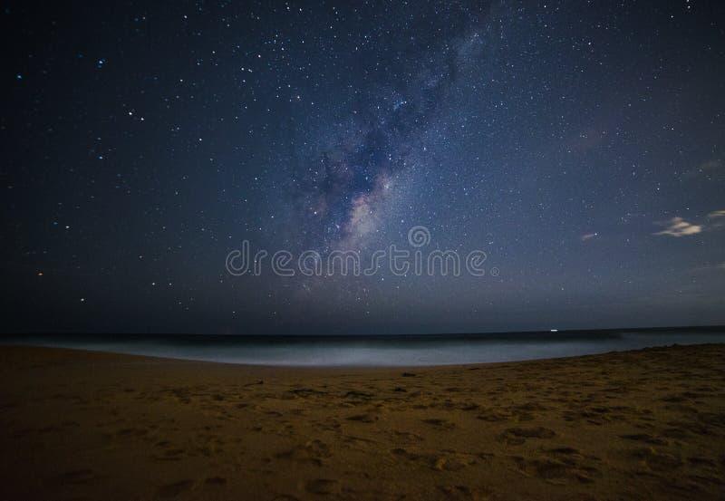 Sken för mjölkaktig väg över havsstranden på natten royaltyfri fotografi