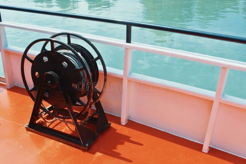 Skeppdetaljer, svart metallsegelbåtvinsch och ett rep på däcket royaltyfri foto