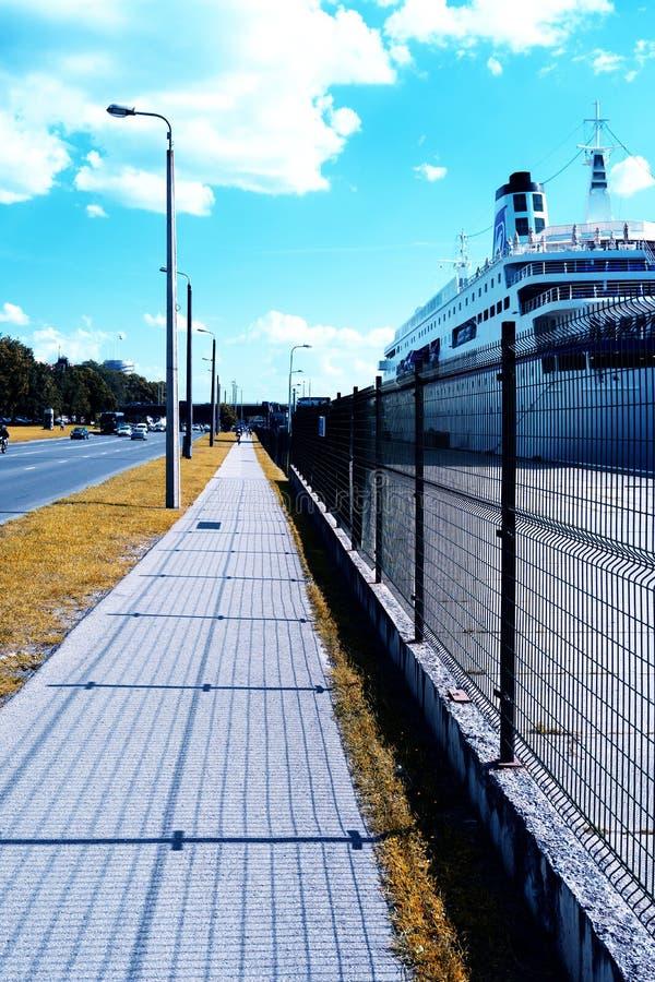 Skeppet förtöjas på kajen bak staketet bredvid vägen arkivfoton