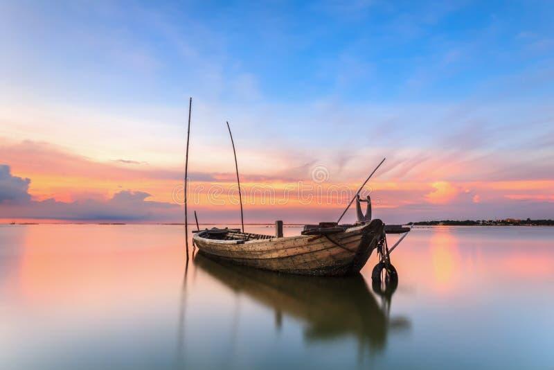 Skeppsbruten fiskebåt på havet med solnedgång i Thailand arkivfoto