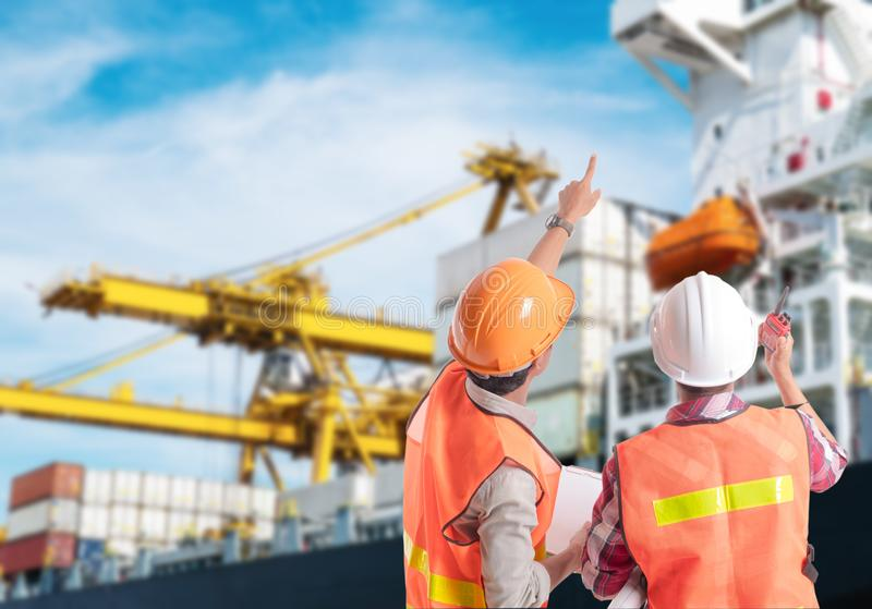 Skeppsdockaarbetare som pekar fingret på kontroll av behållarepäfyllning royaltyfri foto