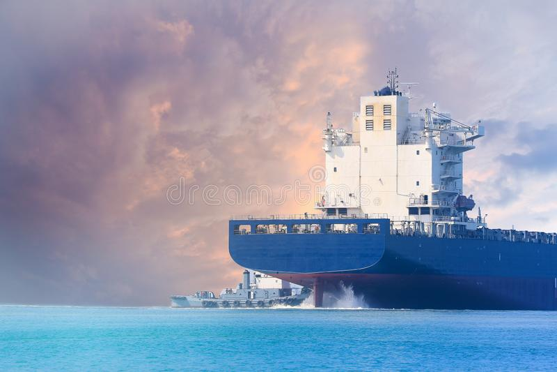 Skeppsegling i havet och bogserbåten som hjälper på det barska skeppet arkivbild