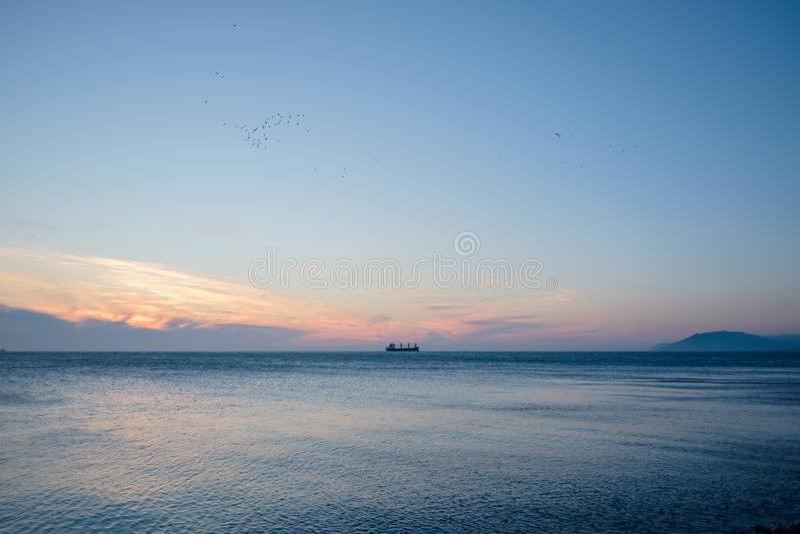 Skeppsegling på horisonten i havet på solnedgången fotografering för bildbyråer