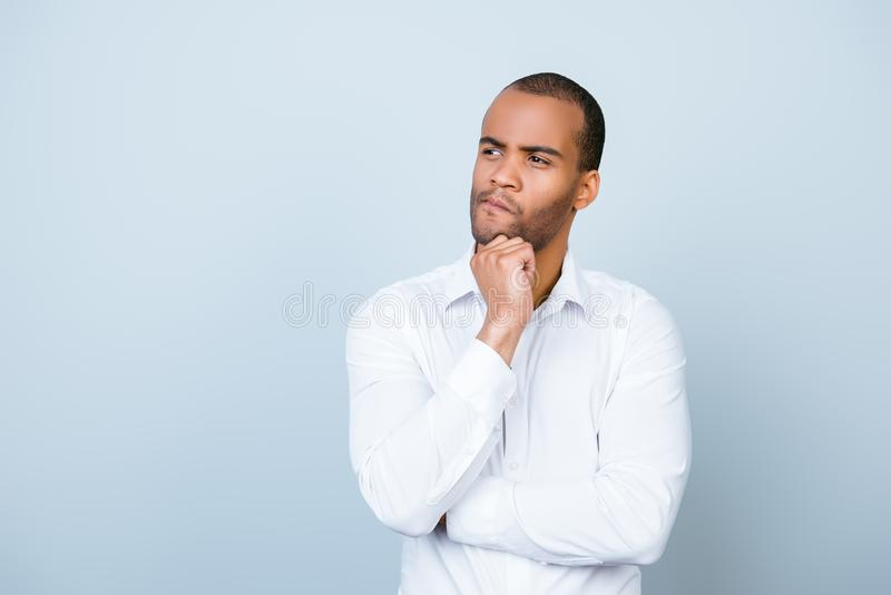 Skeptic, unsure, uncertain, doubts concept. Young african guy in. Formal wear is looking sceptical, has a grimace of distrust on light blue background royalty free stock photos