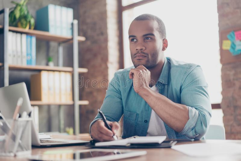 Skeptic, unsure, uncertain, doubts concept. Young african student is making decision sitting at the office in casual smart stock photos