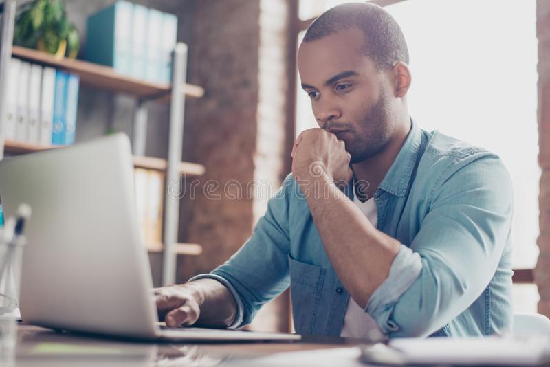 Skeptic young afro freelancer is making decision sitting at the office in casual smart, analyzing the data in the computer stock image
