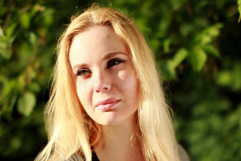 Skeptical blonde in the sunny forest, close-up portrait. stock images