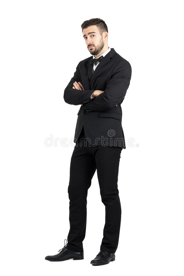 Skeptical defensive man with crossed arms looking at camera suspiciously. Full body length portrait isolated over white studio background royalty free stock photography