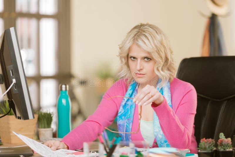 Skeptical kobieta przy Jej biurkiem obrazy royalty free