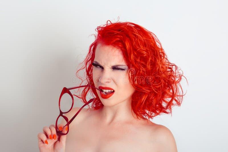 Skeptical kobiety pozować, trzyma szkła zbliża jej usta patrzeje ciebie skeptically kamera obrazy royalty free